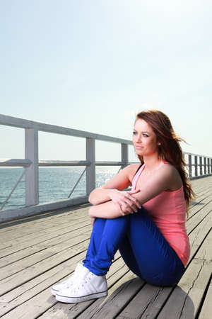 Attractive girl Young woman on pier Sits Relaxing Old Wooden Pier photo
