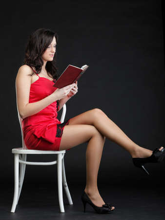 woman read book in red dress chair black background photo
