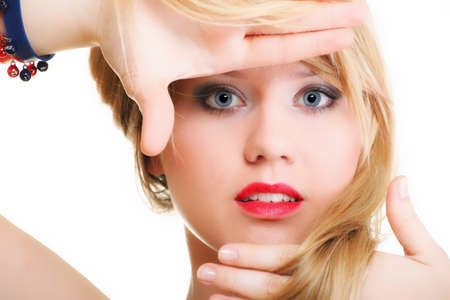 Beautiful woman blonde framing her face with her hands isolated blue eye red lipstick and long blond hair photo
