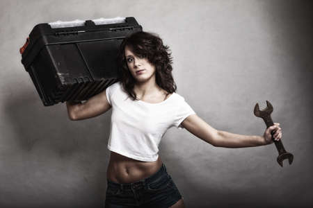 Sex equality and feminism. Sexy girl holding toolbox and wrench spanner tool. Attractive woman working as repairman or mechanic photo
