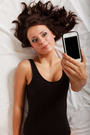 Sexy lazy girl in body underwear lying on the bed taking self photo with mobile phone. Woman relaxing lazing in the bedroom. photo