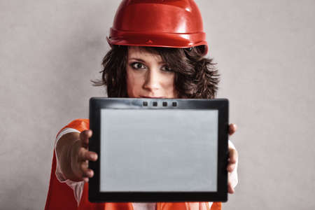 equality and feminism. Sexy girl worker in safety helmet and orange vest showing copy space on tablet touchpad. photo