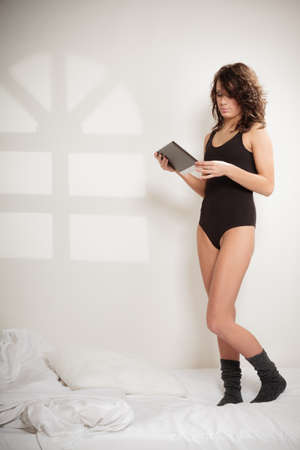 girl in black body underwear using tablet on the bed photo