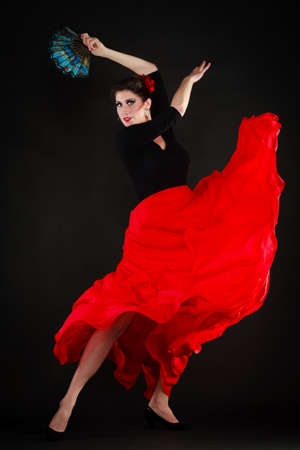 Art. Full length of sexy spanish girl attractive woman in red skirt with fan dancing flamenco traditional dance.