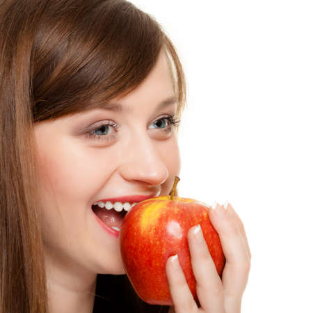 dentalcare: Diet and nutrition. Happy young woman eating biting apple seasonal fruit isolated on white. Girl recommending healthy lifestyle.