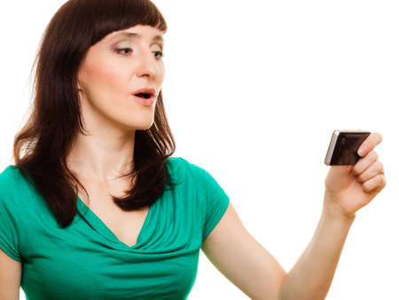 Communication technology. Woman has reaction of surprise as she reads a message on her mobile cell phone, isolate on white photo