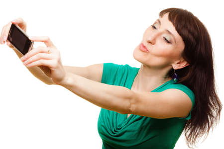 Technology and internet concept - smiling woman taking self picture with smartphone camera isolated photo