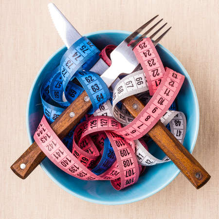 losing control: Diet food healthy lifestyle and slim body concept. Many colorful measuring tapes in blue bowl on table with knife and fork, top view