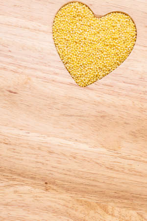 wooden: Dieting concept. Millet groats heart shaped on wooden surface. Healthy food help lower cholesterol.