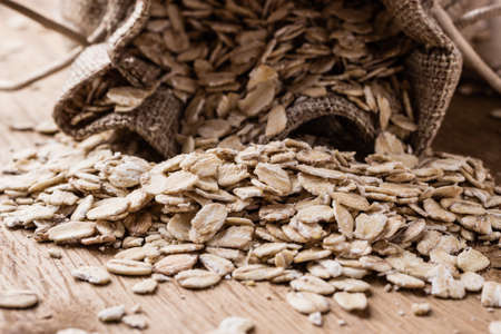 Dieting. Oat cereal in burlap sack on wooden surface. Healthy food for lowering cholesterol, protect heart. Фото со стока
