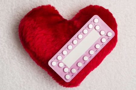 safe sex: Medicine contraception love and birth control. Oral contraceptive pills on red heart shaped little pillow