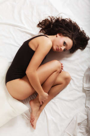 Sad unhappy girl in black body lying in fetal position on bed. Young lonely woman relaxing lazing in bedroom. Depression.