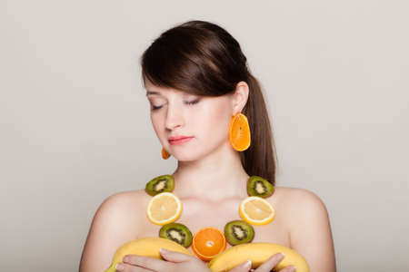 recommending: Diet. Girl with necklace and earrings of fresh citrus fruits holding bananas on gray. Woman recommending healthy nutrition.