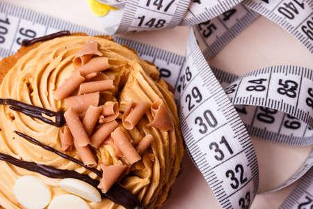 gula: El apetito y el concepto de la gula. Problema de engorde. Magdalena de la torta con cinta m�trica en la mesa Foto de archivo
