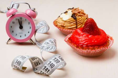 kilos: Gluttony and not eat junk sugar foods concept. Time for slimming. Cake cupcakes measuring tape and alarm clock on kitchen table Stock Photo