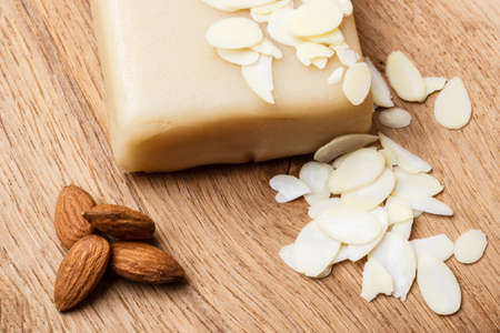 snack food: Whole food, good for health. Marzipan paste sliced blanched almonds and seeds on wooden kitchen board background Stock Photo
