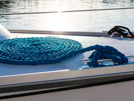 cleat: Blue rope coiled on dock and tied to metal cleat. sailboat yacht detailed part.