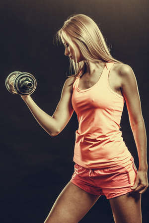 Bodybuilding. Strong fit woman exercising with dumbbells. Muscular blonde girl lifting weights studio shot on dark
