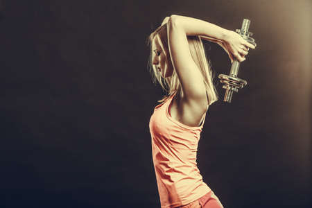 fitness: Bodybuilding. Forte donna adatta che si esercita con manubri. Muscoloso ragazza bionda di sollevamento pesi girato in studio su scuro