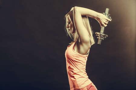 ginástica: Bodybuilding. Mulher forte ajuste exercício com halteres. Levantar pesos menina loura estúdio Muscular tiro na obscuridade