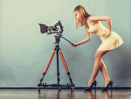 Fotograaf meisje fotograferen. Aantrekkelijke modieuze blonde vrouw in volle lengte nemen van foto's met de camera op blauw