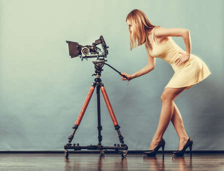 blonde woman: Photographer girl shooting images. Attractive fashionable blonde woman in full length taking photos with camera on blue