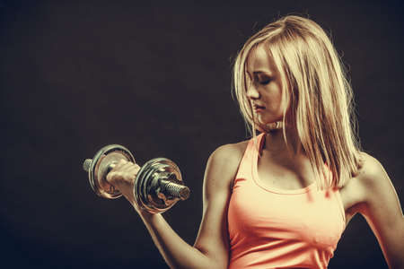 フィットネス: ボディービル。強力なダンベル運動の女性に合います。暗闇で撮影スタジオ重みを持ち上げる筋肉のブロンドの女の子 写真素材