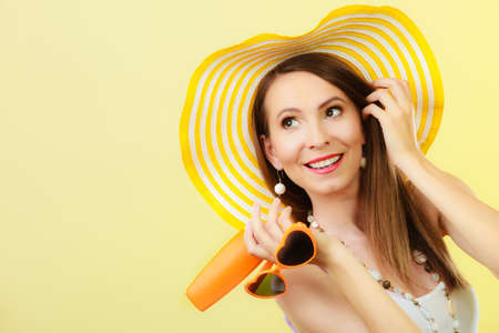 Holidays summer fashion. and skin care concept. Woman in yellow hat holds heart shaped sunglasses sunscreen lotion, bright background copy space Stock Photo