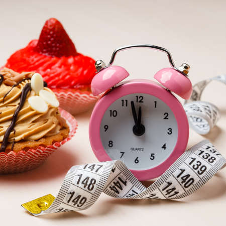 gluttony: Gluttony and not eat junk sugar foods concept. Time for slimming. Cake cupcakes measuring tape and alarm clock on kitchen table Stock Photo