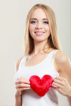 woman chest: Valentines day love relationships or health care concept. Blonde young woman holding red heart love symbol on her chest studio shot on gray Stock Photo
