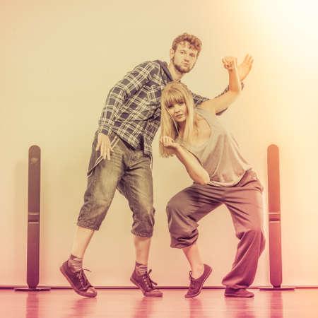 ragazze che ballano: Due ballerini moderni coppia uomo e uomo che balla in garage. Stile di vita urbano. Generazione hip-hop. Archivio Fotografico