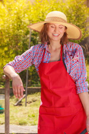 backyard woman: Middle age female with gardening tools outdoors. Woman in hat standing with shovel in her backyard
