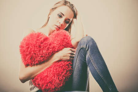Broken heart love concept. Sad unhappy woman hugging red heart pillow closeup 写真素材