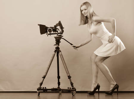 camera: Photographer girl shooting images. Attractive fashionable blonde woman in full length taking photos with camera filtered photo