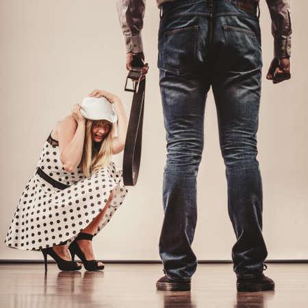 copule: Agresi�n en el problema de la violencia familiar. El hombre golpear a su esposa o novia asustada con la correa. La mujer es v�ctima de abuso dom�stico.