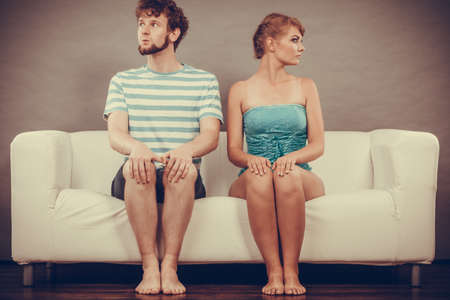 Bad relationship concept. Man and woman in disagreement. Young couple after quarrel sitting offended on couch at home
