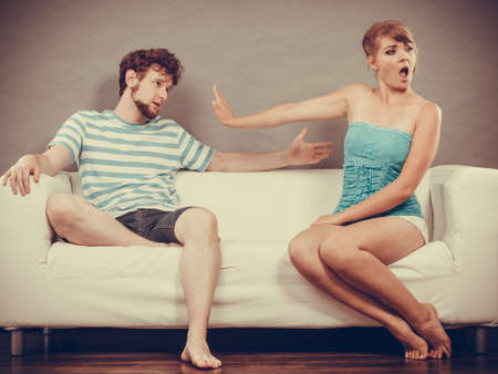 people arguing: Bad relationship concept. Man and woman in disagreement. Young couple sitting on couch at home having quarrel, offended wife and unhappy husband Stock Photo