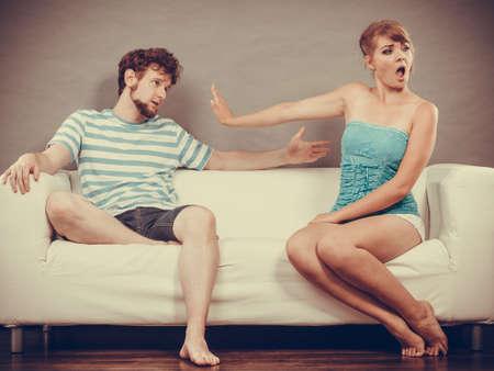 Mala relación de conceptos. Hombre y mujer en desacuerdo. Pareja joven sentado en el sofá en casa con la disputa, la esposa y el marido ofendido infeliz Foto de archivo - 43001582