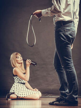 copule: Alcoholism and violence problem. Man beating his wife with belt. Woman addicted to alcohol is victim of domestic abuse