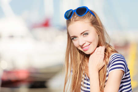sea port: Travel tourism and people concept. Fashion blonde girl with blue heart shaped sunglasses in marina against yachts in port