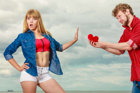 women fight: Love and relationship problem. Woman and man young couple in love outdoor, boyfriend giving his girlfriend red heart love symbol, she refusing gift against sky