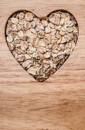 lowering: Dieting healthcare concept. Oat cereal oatmeal heart shaped on wooden surface. Healthy food for lowering cholesterol. Stock Photo
