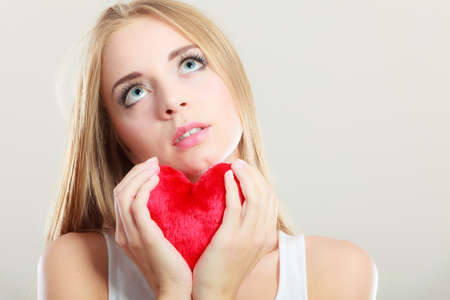 heartbreak issues: Broken heart love concept. Sad unhappy woman holding red heart gray background Stock Photo