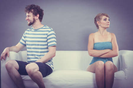 impasse: Bad relationship concept. Man and woman in disagreement. Young couple after quarrel sitting offended on couch