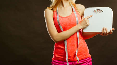 Gym woman with measure tape holding weight scale studio shot black background