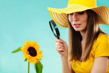 botanist: Botanist woman in yellow hat examining flower looking through magnifying glass on blue background