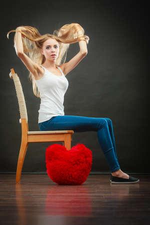 melancholy: Broken heart love concept. Sad melancholy woman sitting on chair red heart pillow on floor dark background Stock Photo