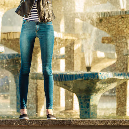 Fashion and people concept. Woman legs in denim trousers casual style outdoor against city fountain