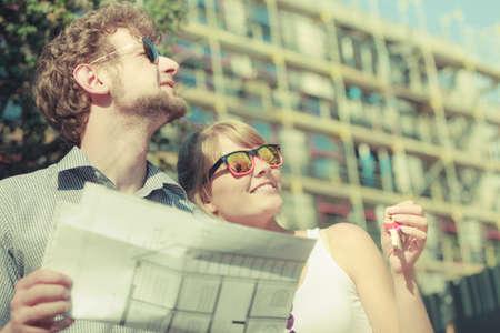 Immobiliare e il concetto di famiglia - giovane coppia sul fronte della nuova grande casa moderna con progetti progetto e chiave sognare casa