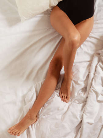 awaking: Closeup of sexy female legs on the bed. Woman lazy girl relaxing lazing in bedroom.